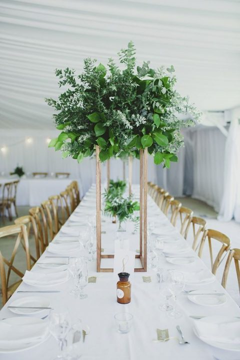 a tall greenery centerpiece of various types of eucalyptus and some foliage on a geometric copper stand