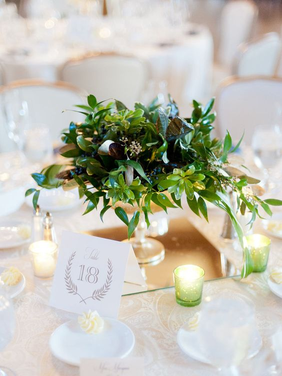a textural greenery wedding centerpiece with various shades of green and dark green