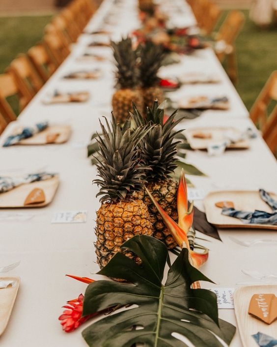a tropical centerpiece version with pineapples and tropical blooms and leaves is a great idea for a modern tropical wedding