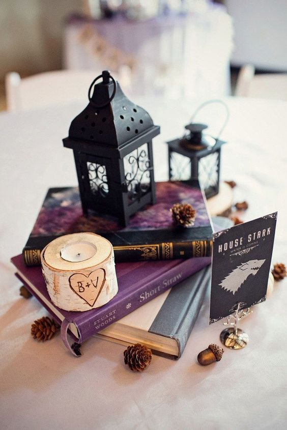 a vintage book centerpiece with small black lanterns, pinecones and a birch candle holder