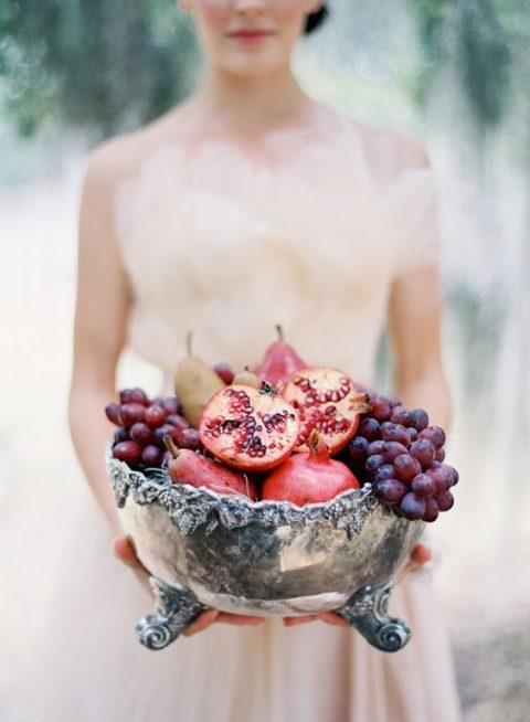 a vintage silver bowl with grapes, pears and pomegranates for a decadent fall wedding