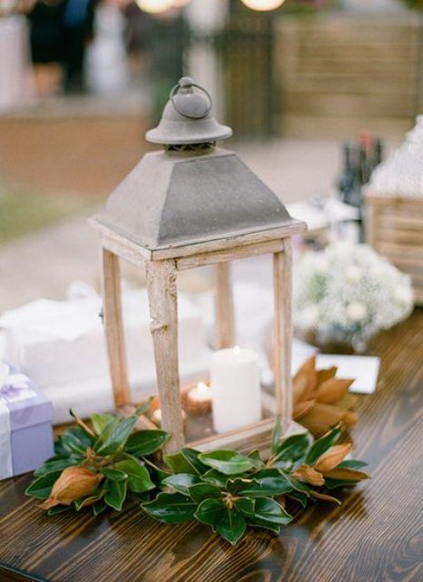 a vintage wooden candle lantern with magnolia leaves and lots of candles inside