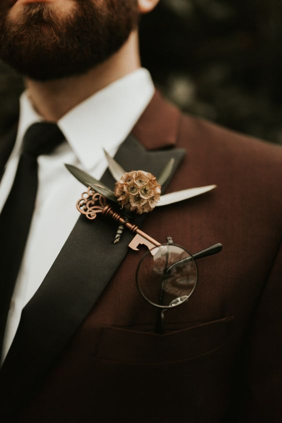a wedding boutonniere of a vintage copper key, a seed pod and greenery is a dreamy idea for a fairy tale wedding or for a Halloween one