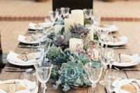 a wedding centerpiece of succulents of various shades and pillar candles is very stylish and chic