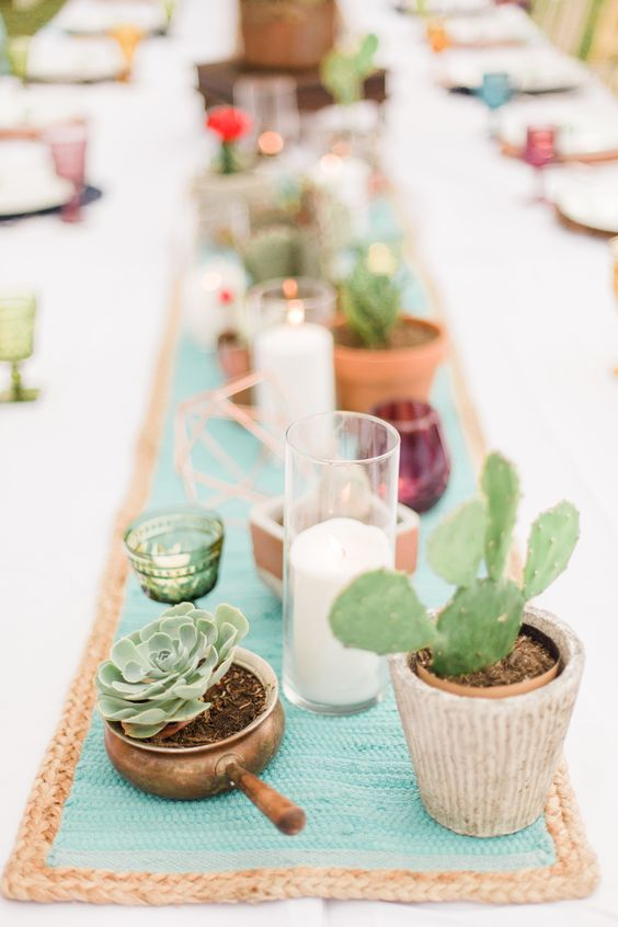 a wedding table runner of candles in glasses, pots with cacti and succulents and copper himmeli