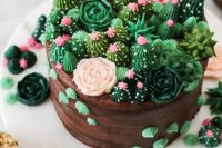 a whimsical chocolate wedding cake topped with sugar cacti and blooms looks very quirky and fun