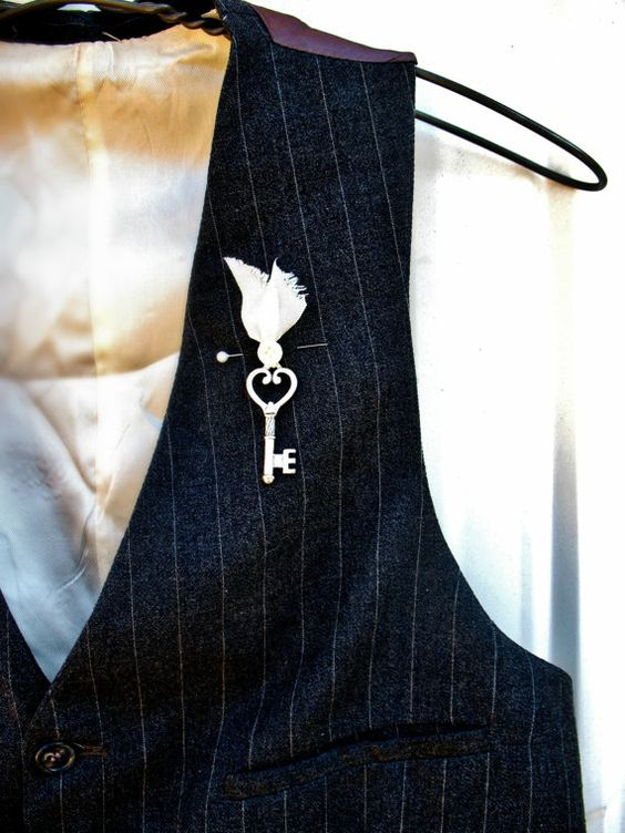 a whimsy boutonniere of a vintage key and a bead in a fabric cover looks vintage and fairy-tale-like at the same time