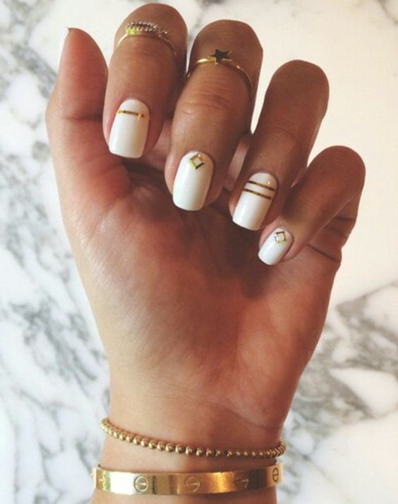a white and gold geometric manicure and some gold rings to accent it will be a very nice solution for a boho bride