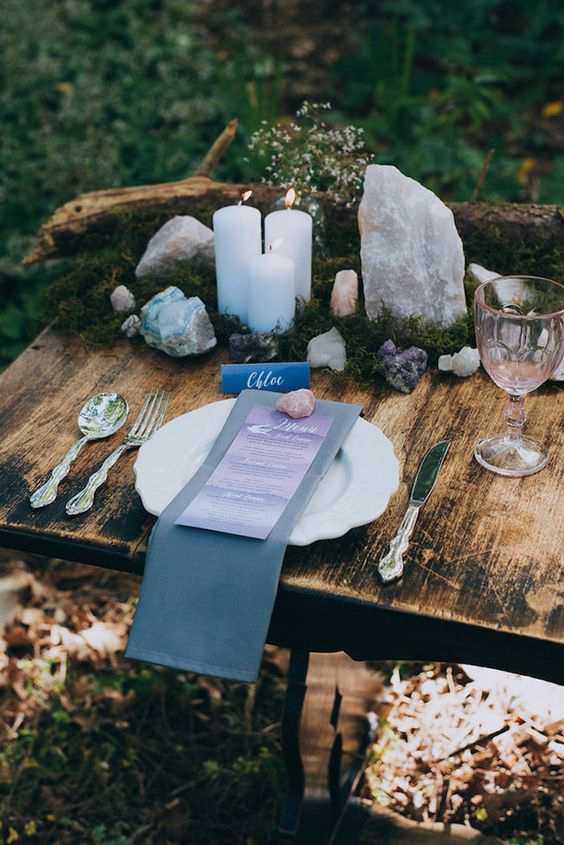 a wild centerpiece of moss, geodes, crystals, pillar candles and a large branch for a woodland wedding