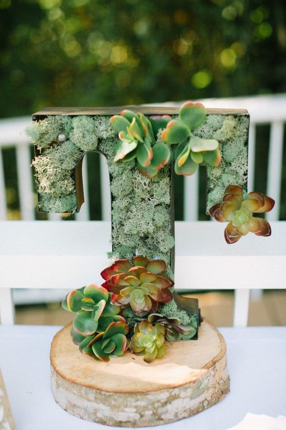 a wood slice, a T letter filled with moss and succulents for a simple rustic centerpiece