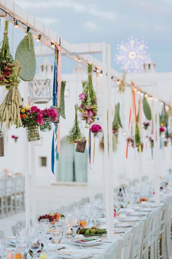an overhead wedding installation with hanging bright blooms, greenery and cacti hanging downs looks creative