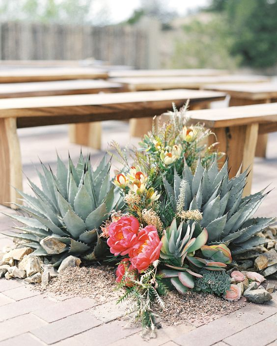 an oversized wedding decoration with oversized succulents, bright blooms and some greenery with wedding venue decor