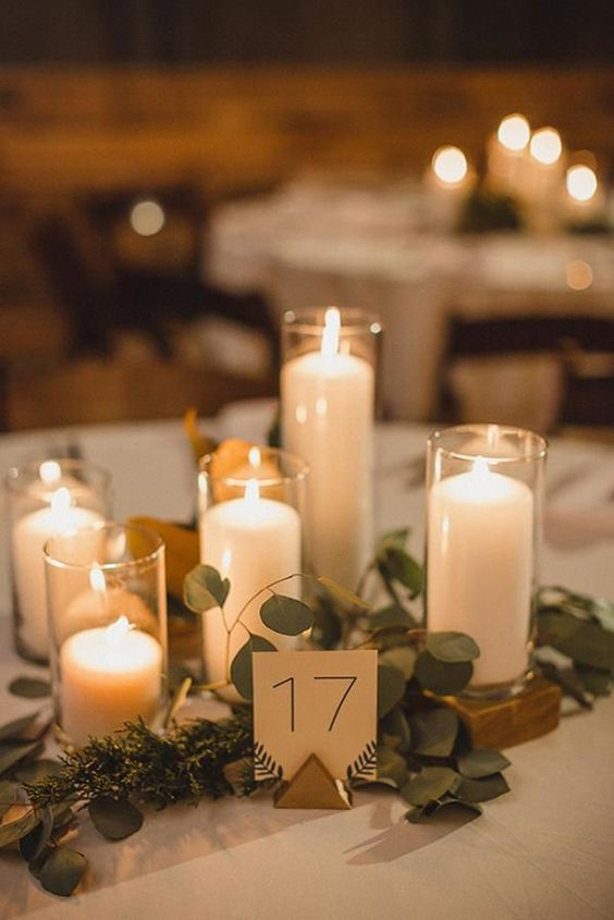 pillar candles in candle holders, fresh greenery and a table number for a simple and chic centerpiece
