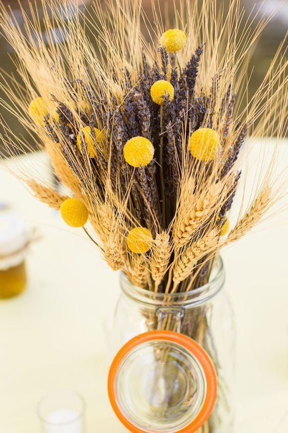 wheat, lavender and craspedia arrangement in a jar won't break the bank and will add a rustic touch to the space