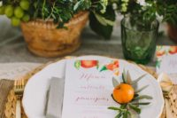a Mediterranean summer wedding tablescape with a woven charger, potted greenery with fruits and gold cutlery