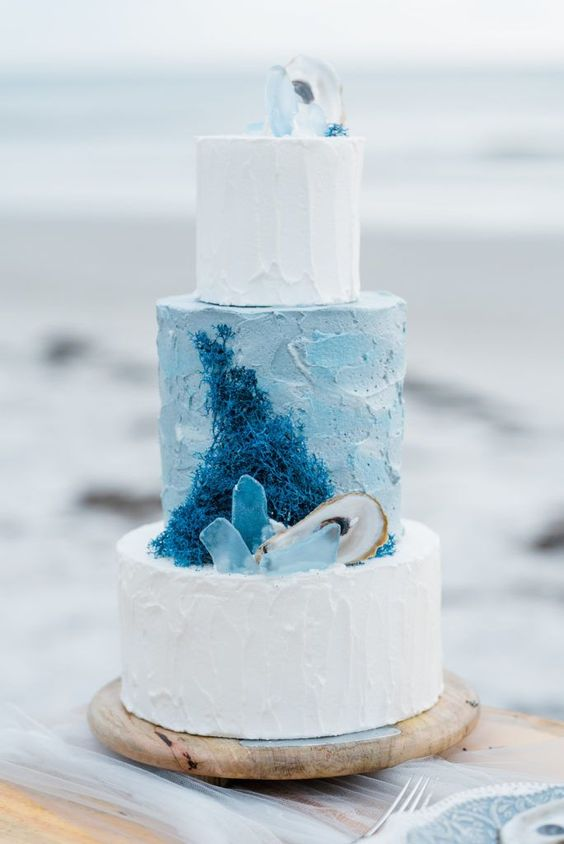 a beach-inspired wedding cake with blue and white textural tiers, with sugar corals, seaglass and seashells is amazing