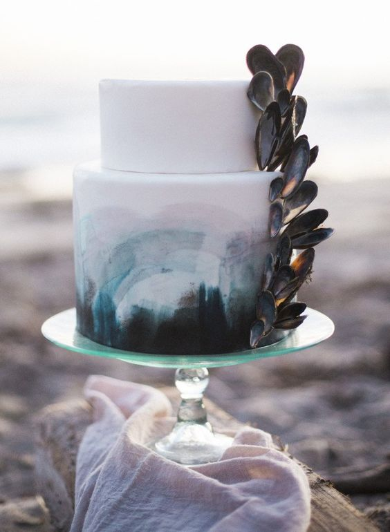 a beach wedding cake in white, with teal, grey and pink brushstrokes and mussel shells attached is wow