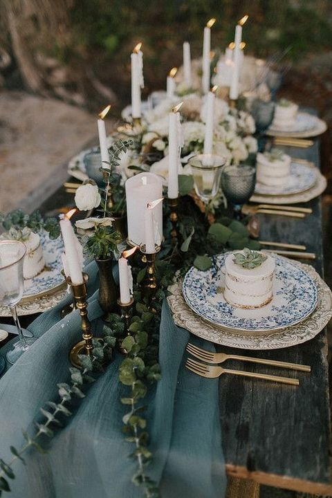 a beach wedding table with a blue runner, eucalyptus, lots of candles, printed plates and mini cakes