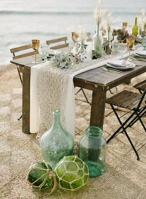 a beach wedding table with a net table runner, dried herbs, air plants, buoys and bottles and metallic goblets