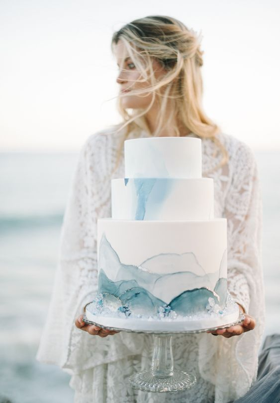 a beautiful coastal wedding cake in white, with blue waves, crystals looks very stylish and chic