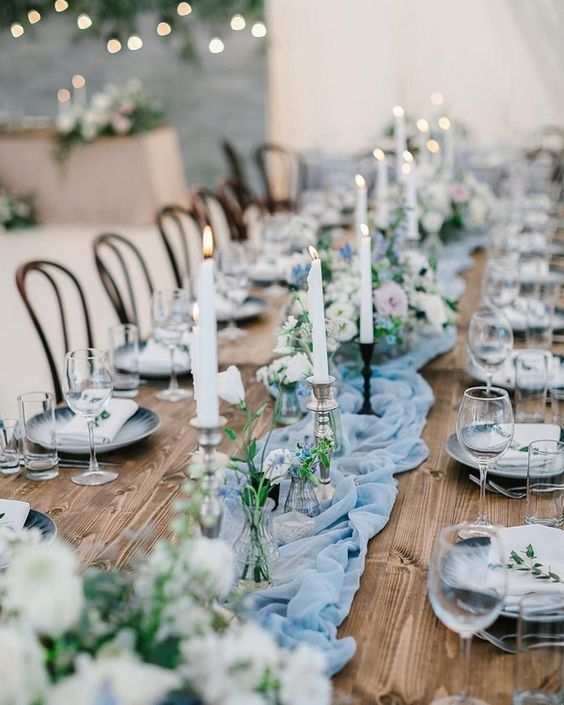a beautiful light blue summer wedding table with a runner, white candles and pastel blooms and grey chargers