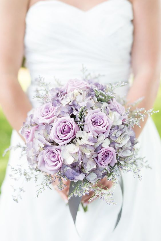 a beautiful lilac and lavender colored wedding bouquet with some pale greenery