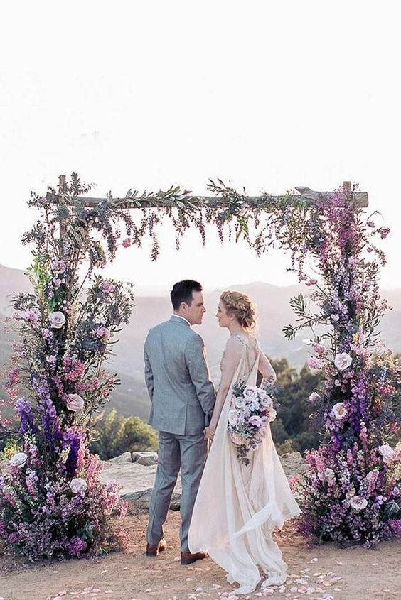 a beautiful lilac and purple wedding arch with lots of blooms plus blush touches and greenery