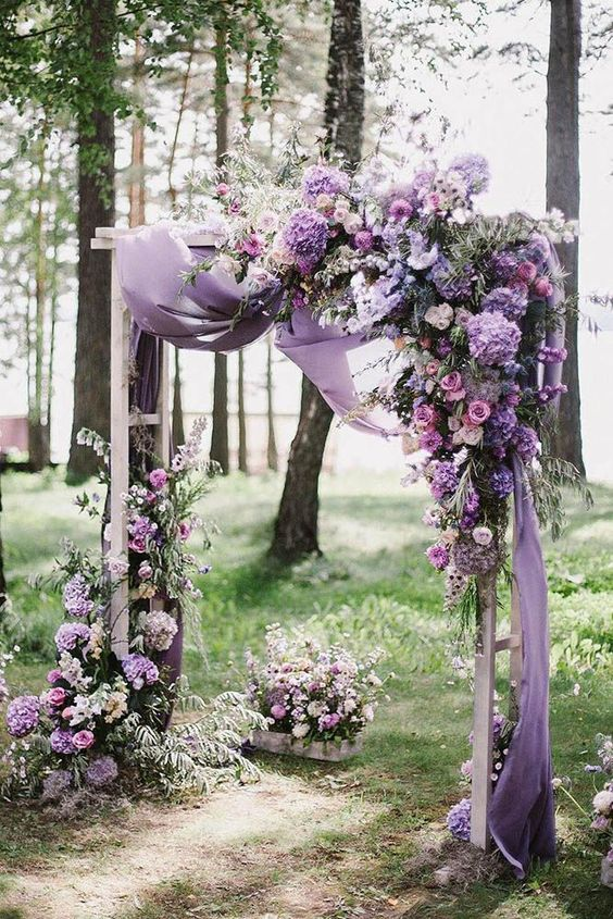 a beautiful lilac and purple wedding arch with lush florals and some airy fabric is amazing for spring and summer