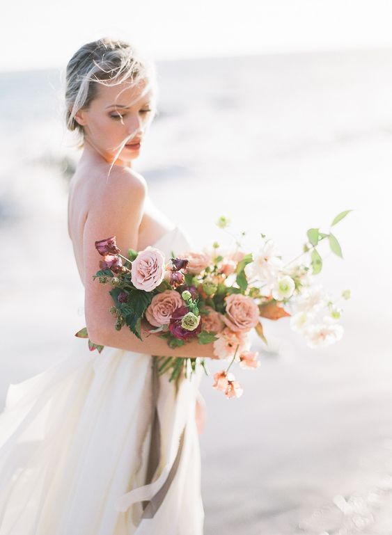 a beautiful pink and purple wedidng bouquet dotted with white blooms and greenery