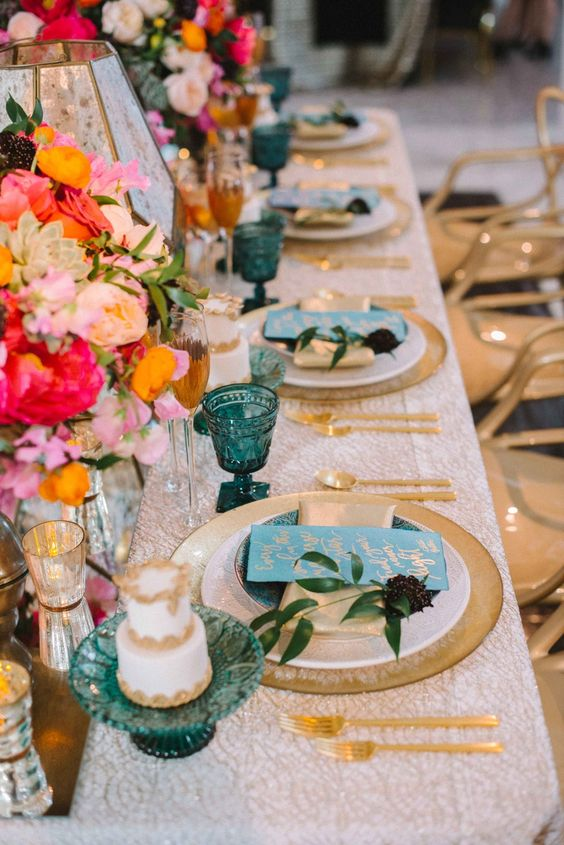a beautiful summer wedding tablescape with a printed tablescape, gold chargers and cutlery, bright blooms and candleholders