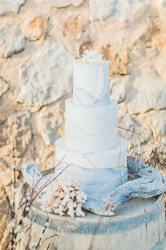 a beautiful white and watercolor blue wedding cake with a gold edge, a coral on top is amazing for a beach wedding