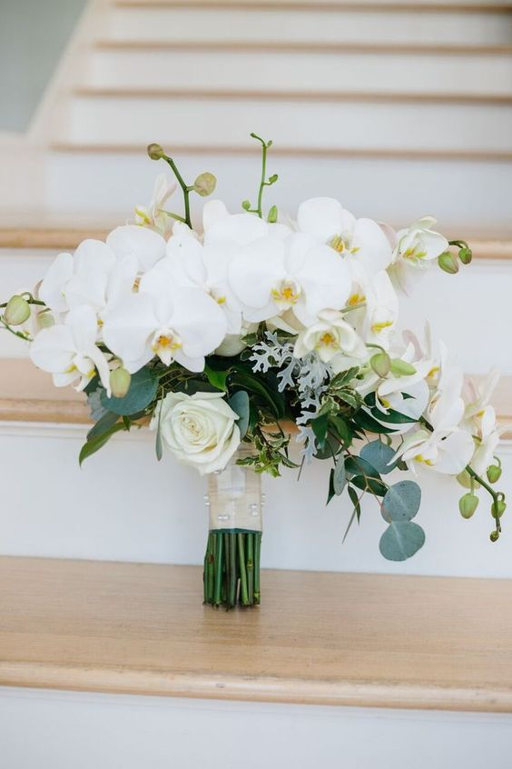 a beautiful white wedding bouquet of orchids and roses, with some greenery is classics