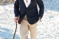 a black jacket, a white shirt, tan pants, grey shoes and a printed handkerchief for a casual and chic outfit