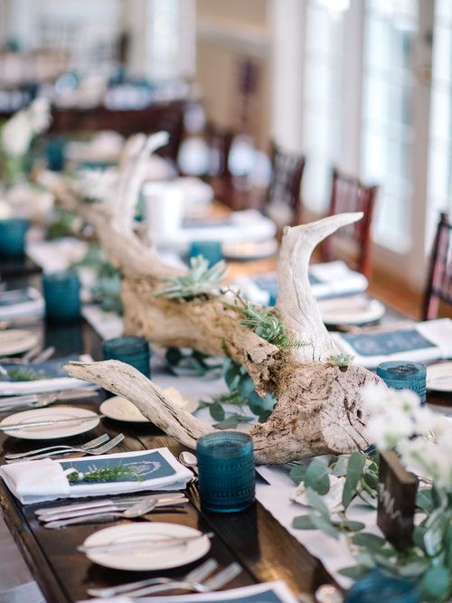 a blue beach wedding table with greenery, driftwood, blue glass candleholders and menus plus succulents and air plants