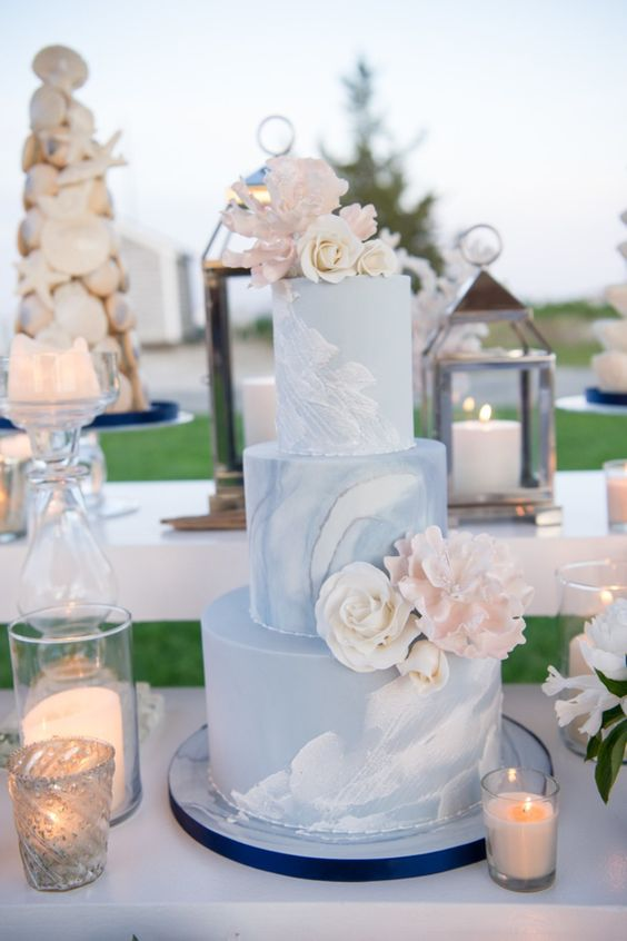 a blue watercolor wedding cake with sugar and real blooms and candles around for a beach wedding dessert table