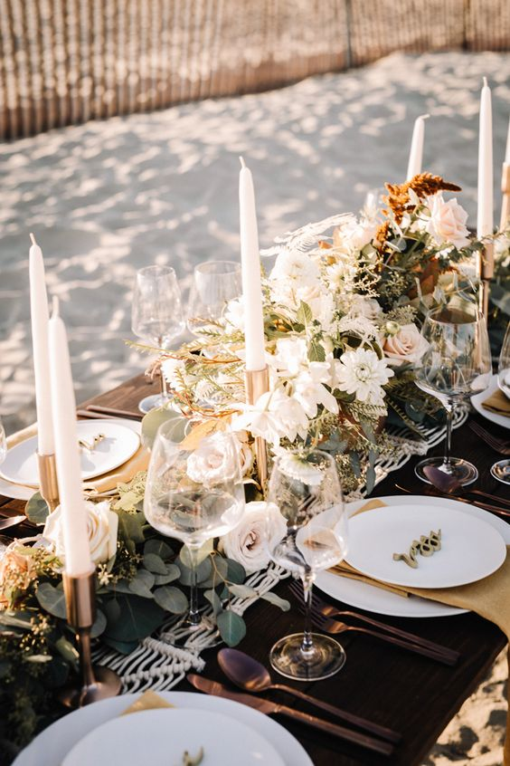 a boho beach wedding table with a macrame runner, greenery and neutral blooms, neutral candles and porcelain
