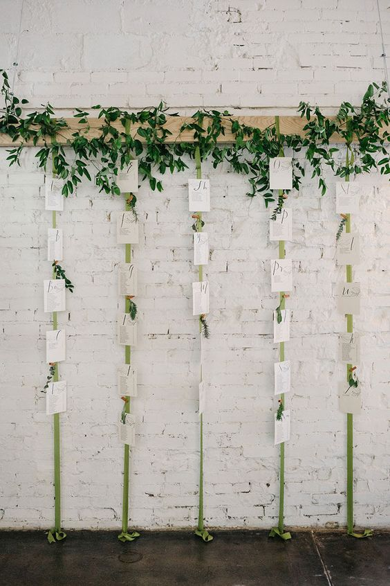 a boho seating chart with greenery and ribbons with a seating plan plus some greenery posies