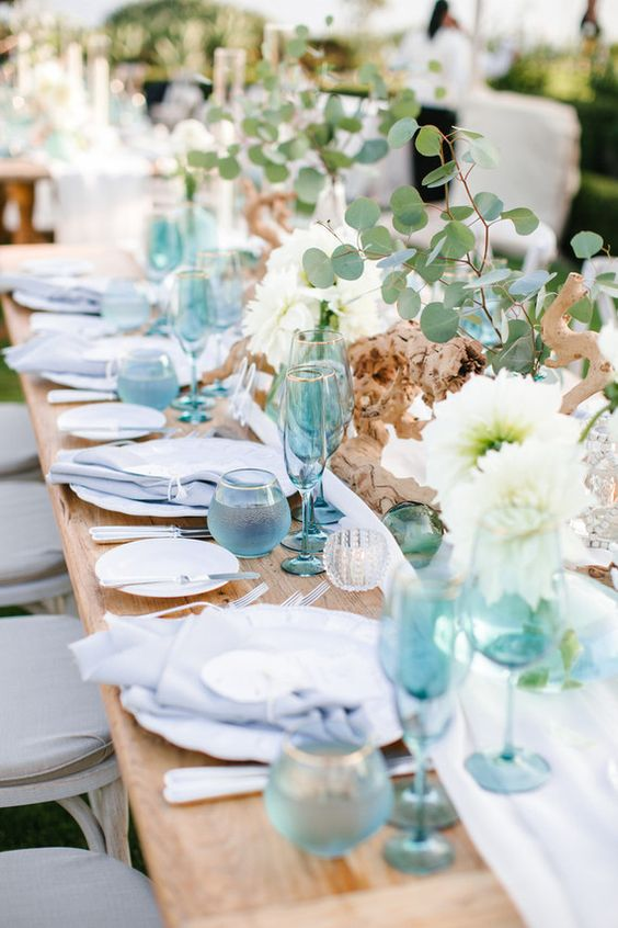 a bold and airy beach wedding tablescape with blue glasses, napkins and porcelain, white blooms, driftwood and greenery