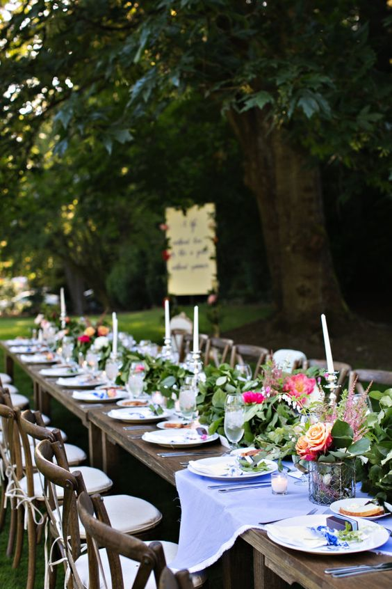 a bold and fresh summer wedding table with lots of greenery, pink blooms, white candles and blue linens