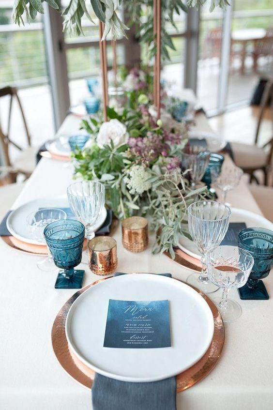 a bold beach wedding tablescape with copper placemats, white porcelain, blue glasses, menus and napkins, greenery and blooms