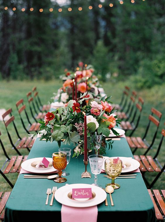 a bold dramatic summer wedding tablescape with a teal tablecloth, pink napkins, bright blooms and greenery and bold candles