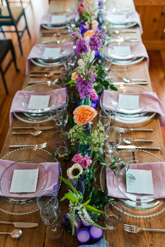 a bold summer wedding tablescape with pink napkins, super bright florals, geodes and purple candles