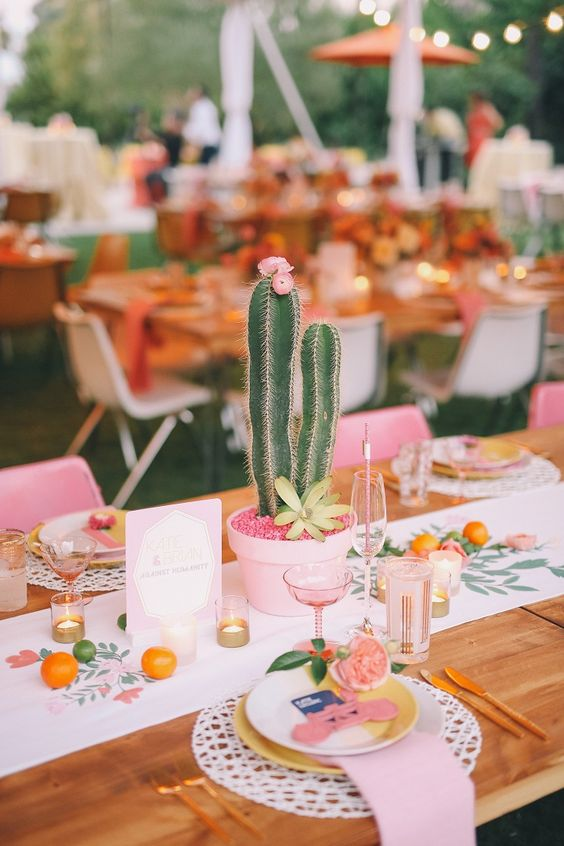 a bright and fun summer wedding tablescape with a printed runner, pink linens, candles and glasses, potted cacti