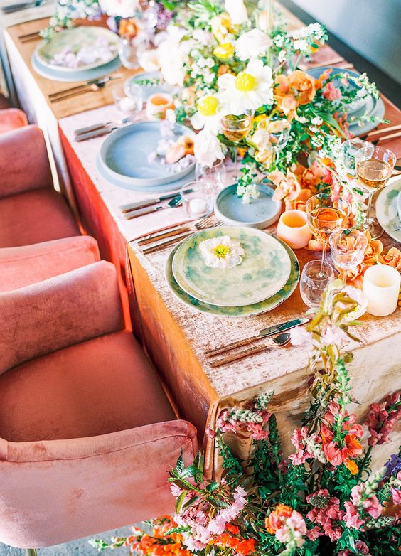 a bright and lush wedding tablescape with lots of lush florals and greenery, with pastel and printed plates and chargers plus candles