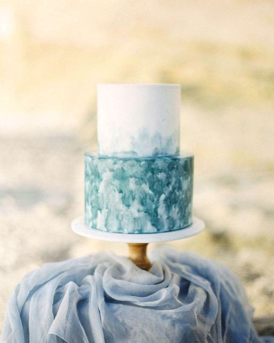 a bright and simple beach wedding cake with a white and watercolro teal tier and no other detailing is amazing