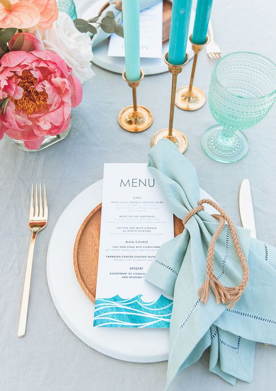 a bright beach table with a light blue tablecloth, turquoise candles, aqua green glasses, a blue napkin, a wooden plate and pink blooms