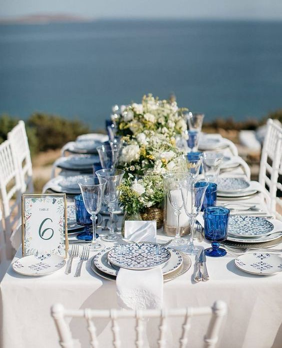 a bright blue beach table with bold glasses, printed plates, neutral floral and greenery centerpieces and a pretty table number