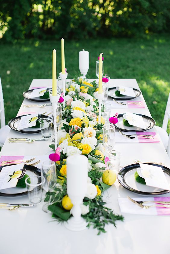 a bright contasting summer wedding table with black and white plates, yellow and white candles, dip dyed napkins and yellow blooms