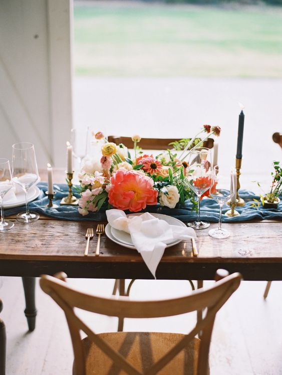 a bright summer wedding table with a blue runner, bright florals, colorful candles and white napkins