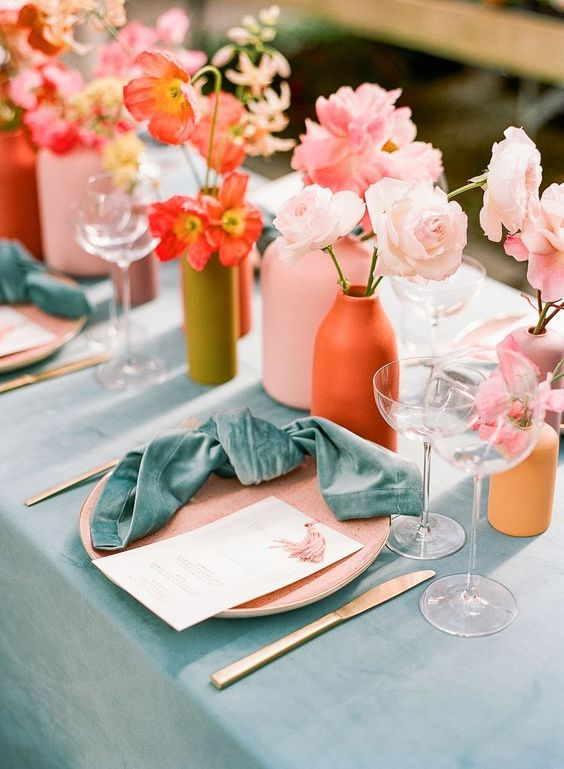 a bright summer wedding table with pink and red blooms, blue linens, colorful vases and candles and gold cutlery